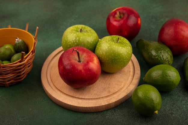 Bovenaanzicht van smakelijke rode en groene appels op een houten keukenbord met feijoas op een emmer met limoenen avocado geïsoleerd op een groen oppervlak