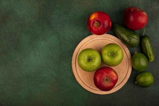 Bovenaanzicht van smakelijke rode en groene appels op een houten keukenbord met limoenen, avocado en komkommer geïsoleerd op een groene muur met kopie ruimte