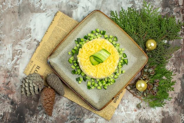 Bovenaanzicht van smakelijke salade geserveerd met gehakte komkommer en mesvork op een oude krant