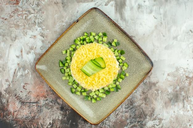 Bovenaanzicht van smakelijke salade geserveerd met gehakte komkommer op gemengde kleur achtergrond