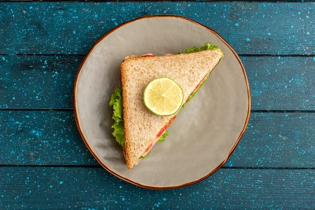 Bovenaanzicht van smakelijke sandwich met groene salade tomaten op het blauwe bureau