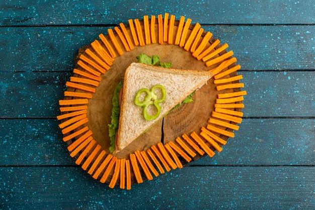 Bovenaanzicht van smakelijke sandwich met oranje beschuit op het blauwe bureau