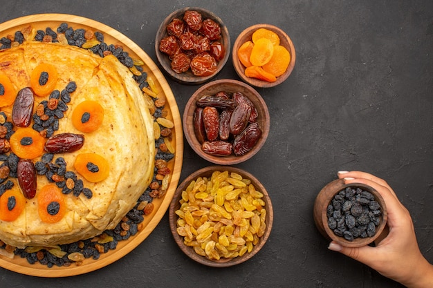 Bovenaanzicht van smakelijke shakh plov gekookte rijst binnen rond deeg met rozijnen op grijze ondergrond