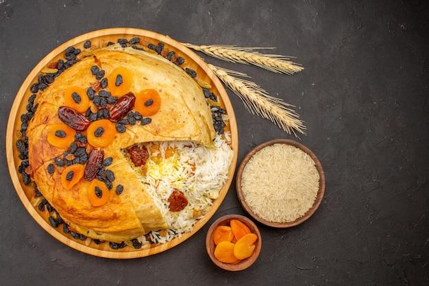 Bovenaanzicht van smakelijke shakh plov met rozijnen en gedroogde abrikozen op het donkere oppervlak