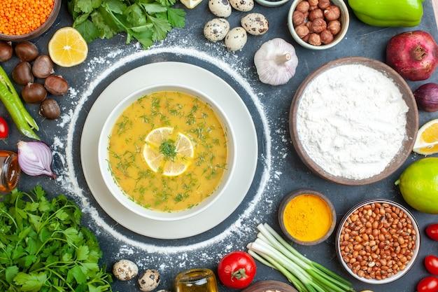 Bovenaanzicht van smakelijke soep geserveerd met citroen en groen in een witte kom en bloem tomatenolie fles bloem groen bundelt eieren op donker