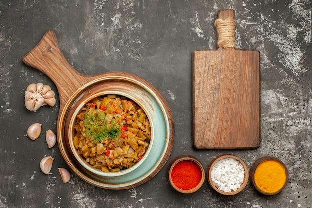 Bovenaanzicht van smakelijke sperziebonen en smakelijke sperziebonen en tomaten op de houten plank kommen met kruiden knoflook en snijplank