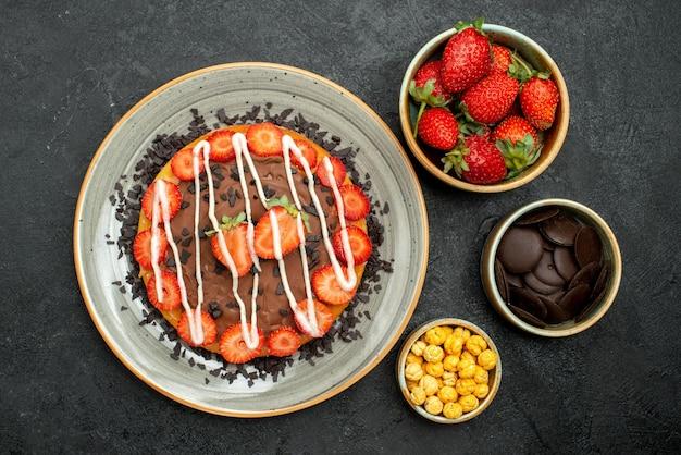 Bovenaanzicht van smakelijke taartplaat van taart met chocolade en aardbei naast kommen met aardbei-hazelnoot en chocolade op donkere tafel