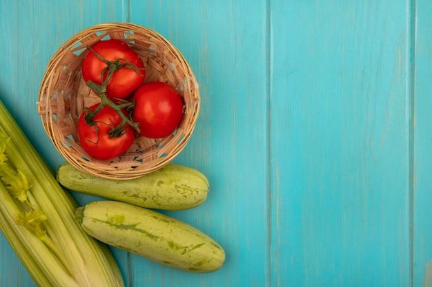 Bovenaanzicht van smakelijke tomaten op een emmer met courgettes en selderij geïsoleerd op een blauwe houten oppervlak met kopie ruimte