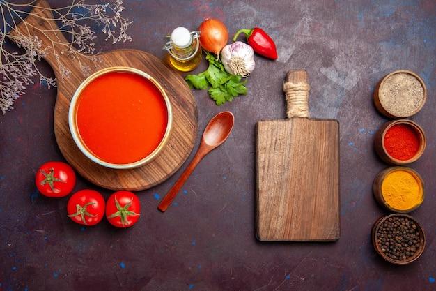 Bovenaanzicht van smakelijke tomatensoep met kruiden op dark