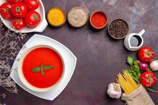 Bovenaanzicht van smakelijke tomatensoep met verse rode tomaten en kruiden op dark on