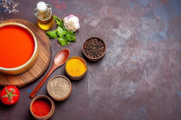 Bovenaanzicht van smakelijke tomatensoep met verse tomaten en kruiden op dark on