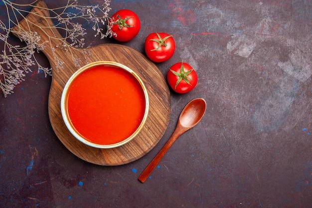 Bovenaanzicht van smakelijke tomatensoep met verse tomaten op dark
