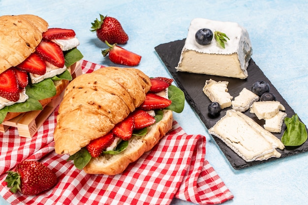 Bovenaanzicht van smakelijke versgebakken croissants met zachte kaas en verse aardbeien.