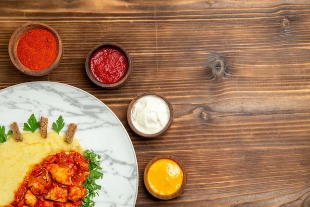 Bovenaanzicht van smakelijke vleesplakken met aardappelpuree en smaakmakers op bruine tafel