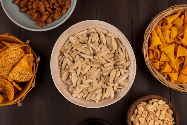 Bovenaanzicht van smakelijke witte zonnebloempitten op een kom met pittige chips op een emmer met maïs snacks op een emmer op een houten tafel