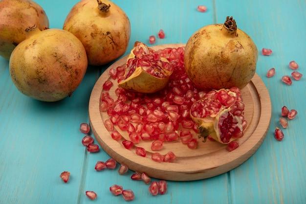 Bovenaanzicht van smakelijke zoete granaatappels met zaden geïsoleerd op een houten keukenplank met mes op een blauwe houten oppervlak