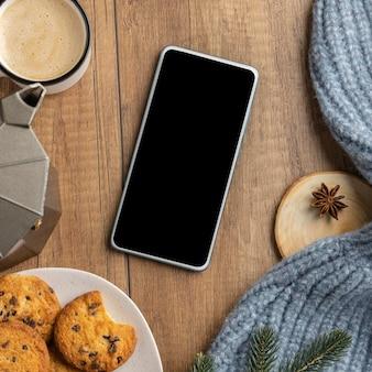 Bovenaanzicht van smartphone met koekjes en kopje koffie