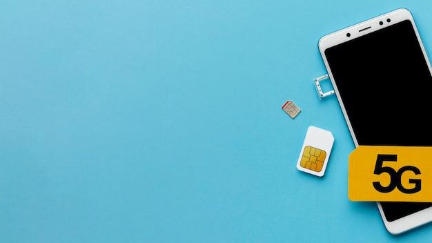 Bovenaanzicht van smartphone met simkaart en kopie ruimte