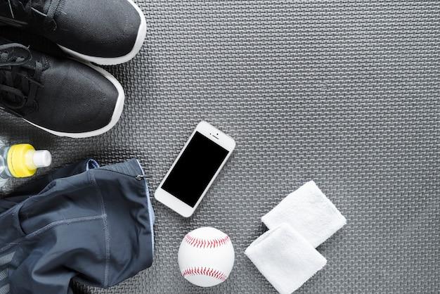 Bovenaanzicht van smartphone omgeven met sportkleding