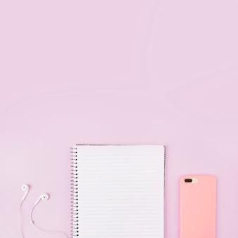 Bovenaanzicht van smartphone; oortelefoon en blocnote aan de rand van roze achtergrond