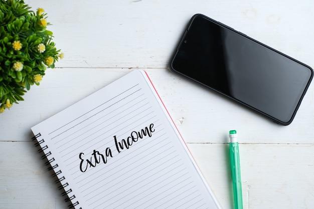 Bovenaanzicht van smartphone, plant, pen met handschrift 'declutter your life' op notebook over witte houten achtergrond.
