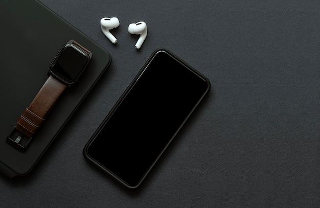 Bovenaanzicht van smartphone, smartwatch en oortelefoon met zwart scherm op zwart lederen oppervlak