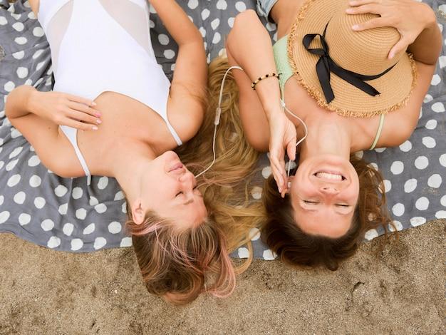 Bovenaanzicht van smileyvrienden ontspannen op het strand