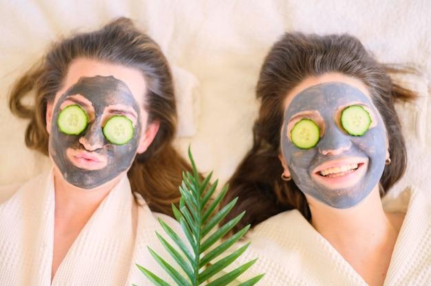 Bovenaanzicht van smileyvrouwen met gezichtsmaskers en plakjes komkommer op hun ogen