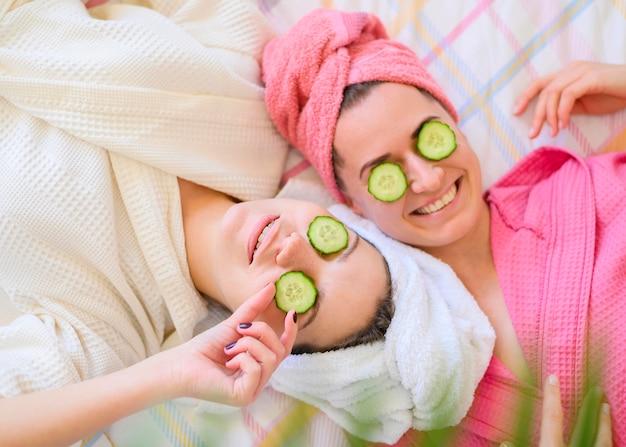 Bovenaanzicht van smileyvrouwen met plakjes komkommer op ogen