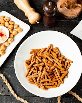 Bovenaanzicht van snack voor bier crackers van brood in een plaat op zwart