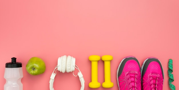 Bovenaanzicht van sneakers met gewichten en koptelefoon