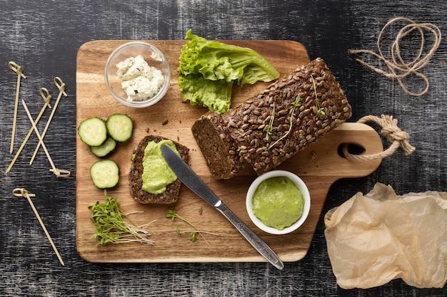 Bovenaanzicht van sneetjes brood voor sandwiches met komkommers