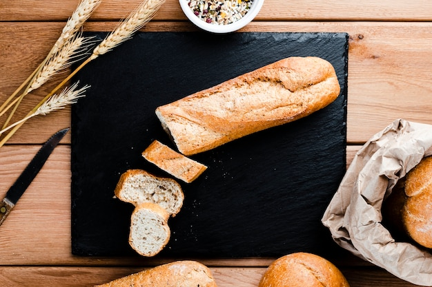 Bovenaanzicht van sneetjes en brood op woden tafel