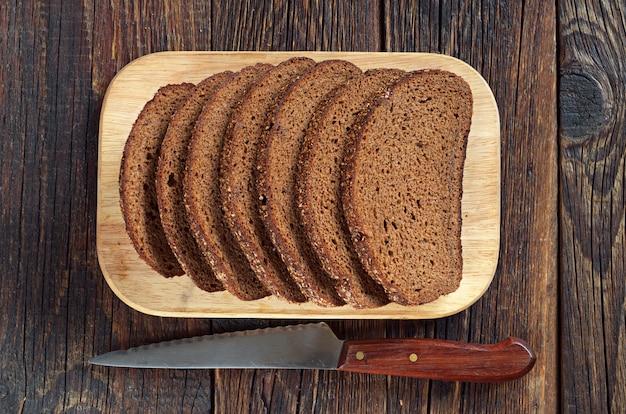 Bovenaanzicht van sneetjes zwart brood op snijplank