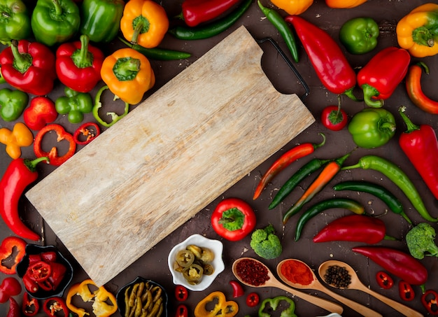 Bovenaanzicht van snijplank en groenten als peper, broccoli, kruiden op kastanjebruine achtergrond