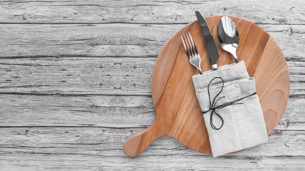 Bovenaanzicht van snijplank met bestek verpakt in doek