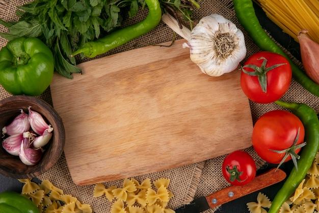 Bovenaanzicht van snijplank met tomaten knoflook bell en hete pepers en uien met munt op een beige servet