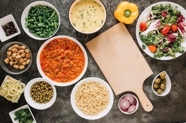 Bovenaanzicht van snijplank met uien en salade