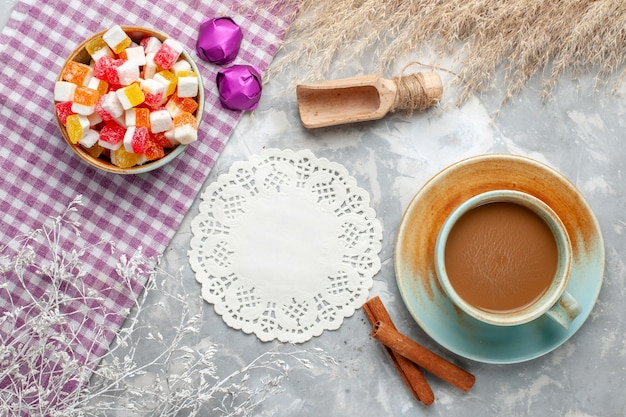 Bovenaanzicht van snoepjes en kaneel samen met melkkoffie op licht bureau, snoep bonbon zoete suiker
