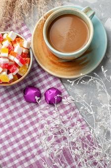 Bovenaanzicht van snoepjes met koffie op licht bureau, snoep bonbon zoete suiker