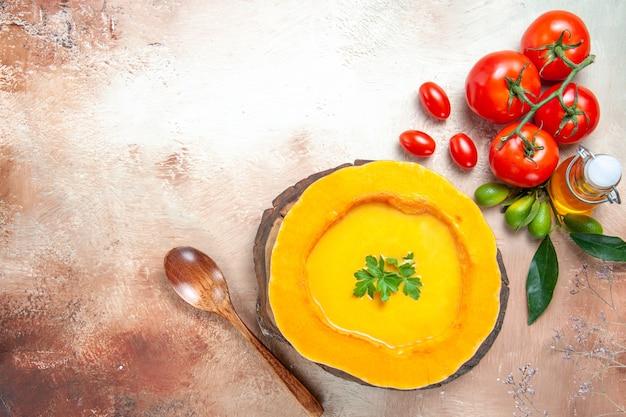 Bovenaanzicht van soep pompoensoep op het bord lepel tomaten citrusvruchten met bladeren olie