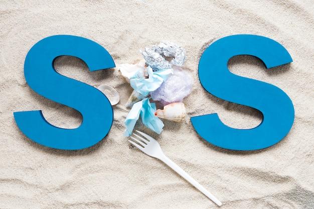 Bovenaanzicht van sos op strandzand met plastic en schelpen