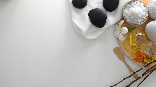 Bovenaanzicht van spa-behandeling en relax concept met aroma-olie, spa-zout, hete steen en andere spa-accessoires