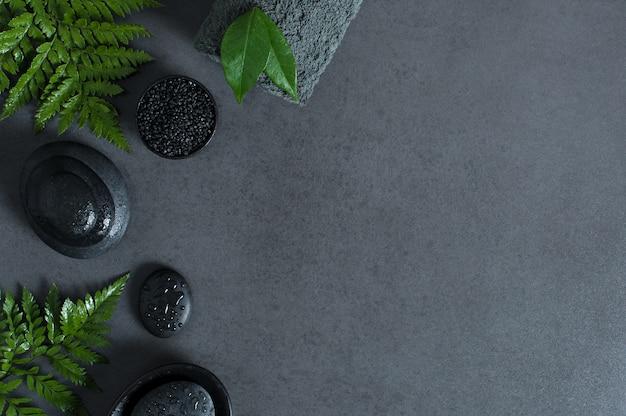 Bovenaanzicht van spa omgeving met hete stenen en groene varens op grijze achtergrond met kopie sapce.