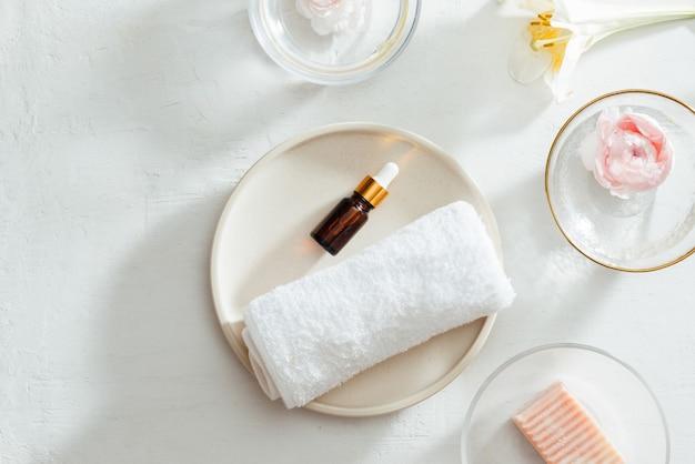 Bovenaanzicht van spa-producten met handdoek en olie op bord, bloemen, zeep op witte achtergrond