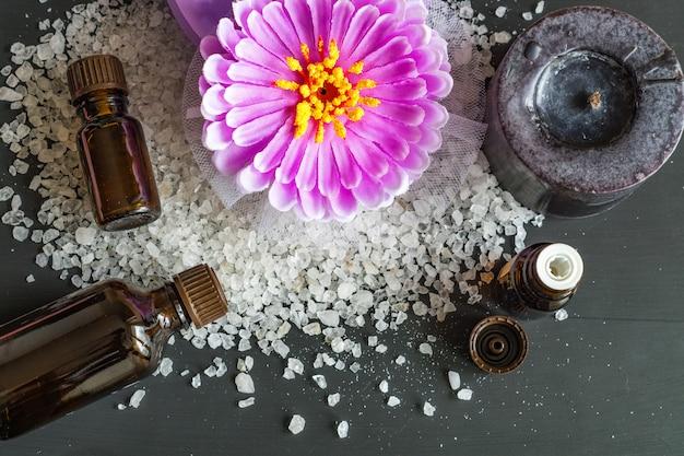 Bovenaanzicht van spa teraetments - zeezout, aroma etherische oliën op zwarte houten achtergrond