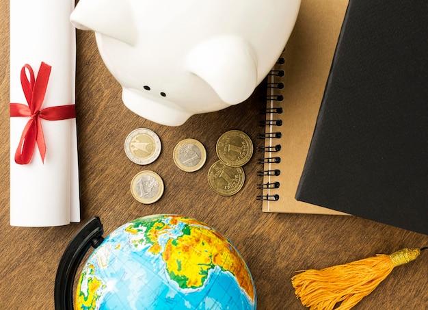 Bovenaanzicht van spaarvarken met notebooks en diploma