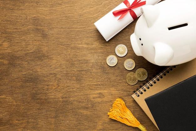 Bovenaanzicht van spaarvarken met notitieboekjes en munten