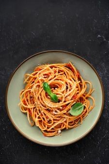 Bovenaanzicht van spaghetti met tomatensaus op zwarte achtergrond