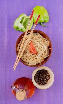Bovenaanzicht van spaghetti pasta met plakje tomaat en eetstokjes in kom met half gesneden peper zwarte peper gesmolten boter op paarse achtergrond